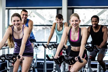 adentro y afuera: Las personas en forma que se resuelven en clase de spinning en el gimnasio Foto de archivo