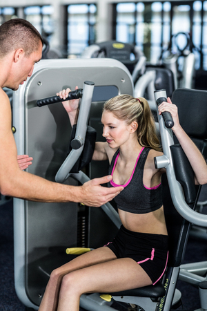 exercise machine: Trainer motivating woman while using exercise machine at the gym Stock Photo