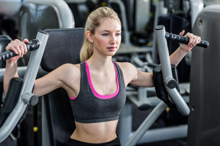 exercise machine: Fit woman using exercise machine at the gym
