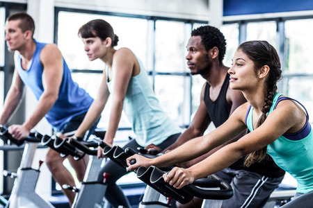 Las personas en forma que se resuelven en clase de spinning en el gimnasio Foto de archivo - 50602895