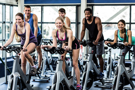 exercise bike: Fit people working out at spinning class in the gym
