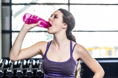sediento: Mujer sedienta de agua potable en la pelota de ejercicio en el gimnasio