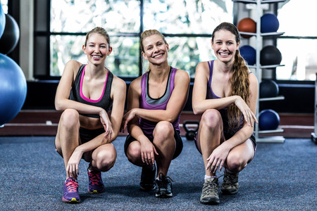 Happy female friends crouching together in gym