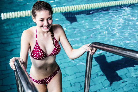 getting out: Smiling young woman getting out the pool Stock Photo