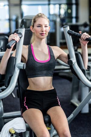 Ajustar la mujer que usa la máquina de ejercicio en el gimnasio