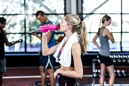 Blonde woman drinking water after working out in the gym