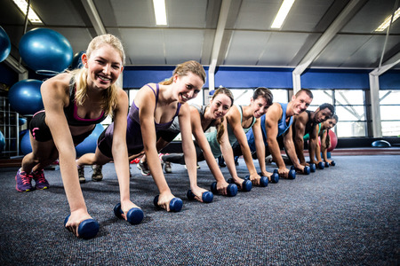 plank position: Fitness class in plank position with dumbbells at the gym