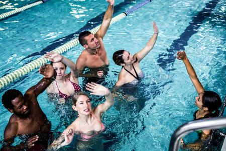 Fitness group doing aqua aerobics in the pool