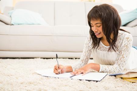 persona escribiendo: Mujer sonriente que trabaja en el piso en la sala de estar