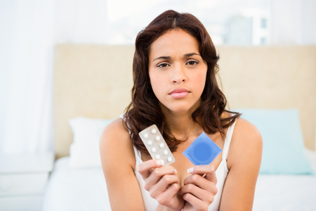 Concerned woman looking at contraception at home
