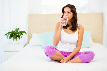 glass bed: Happy woman holding glass of water while sitting on bed at home