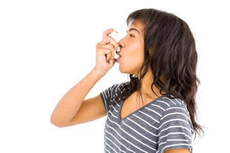 asthma: Mujer ocasional que usa su inhalador contra el fondo blanco Foto de archivo