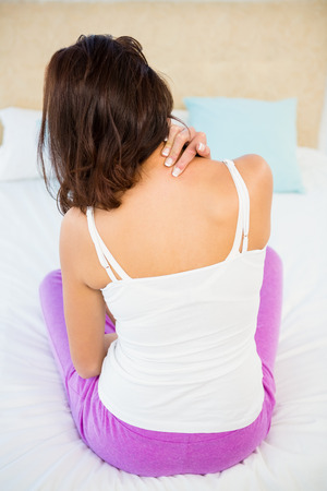 spinal conditions: Rear view of a woman with neck pain at home Stock Photo