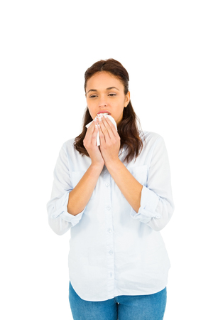 blowing nose: Woman blowing nose with tissue paper against white background