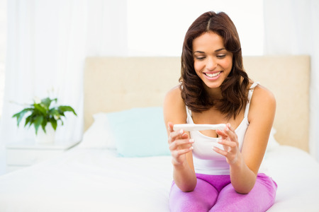 home pregnancy test: Happy woman looking at her pregnancy test at home Stock Photo