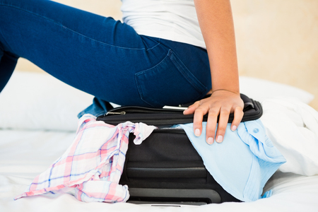 forcing bed: Woman sitting on her overfull suitcase at home