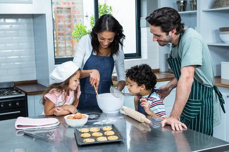 Familia feliz que cocina galletas juntos en la cocina en el hogar