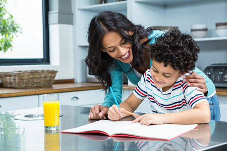 learning by doing: Kind mother helping her son doing homework in kitchen Stock Photo