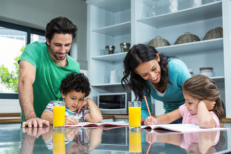 family with two children: Parents helping their children doing homework in the kitchen
