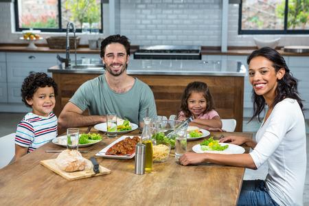 familia comiendo: retrato de familia feliz comiendo juntos en la cocina Foto de archivo