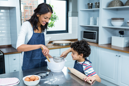 family with one child: Smiling mother cooking with her son in kitchen at home