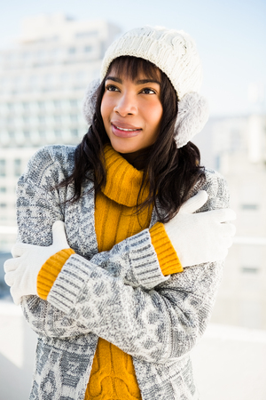 shivering: Smiling woman wearing winter clothes with arms crossed outside Stock Photo