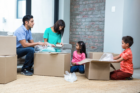 family  room: Happy family opening boxes in living room Stock Photo
