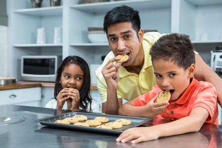 niños desayunando: Sonriente padre con sus hijos comiendo galletas en la cocina en casa Foto de archivo