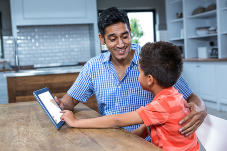 Smiling father using tablet with his son in the kitchen