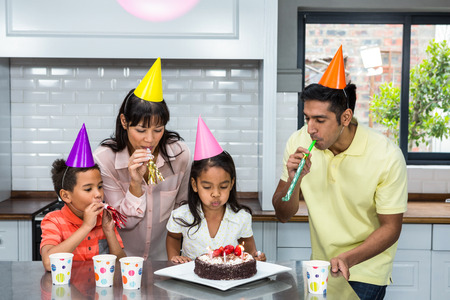 party hat: Happy family celebrating a birthday at home in the kitchen