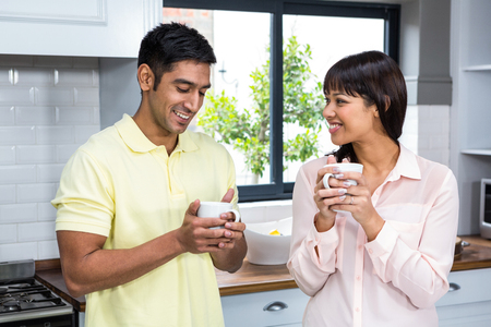 Happy couple talking and holding cups in the kitchen