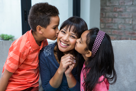 living being: Happy mother being kissed by her children in living room