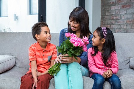 gifting: Happy mother holding roses sitting with her son and daughter on the sofa in living room