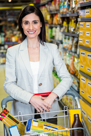 aisle: Smiling woman pushing trolley in aisle in supermarket