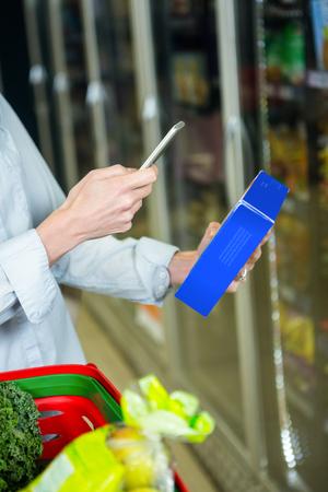 tomando refresco: Mujer que toma la foto de una caja en el supermercado
