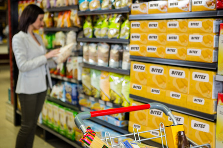aisle: Woman looking at product in aisle at supermarket
