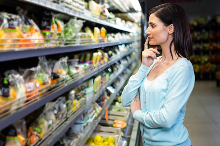 picking fingers: Smiling woman picking vegetables in supermarket Stock Photo