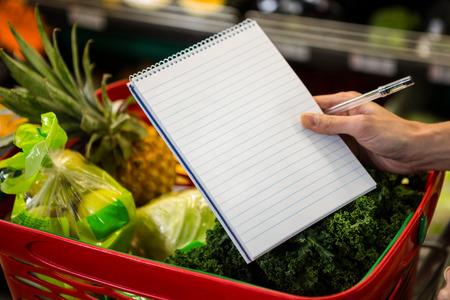 abarrotes: Cierre de vista de una lista de compras contra una cesta llena Foto de archivo