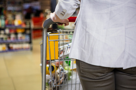 cropped: Cropped image of woman pushing trolley in supermarket