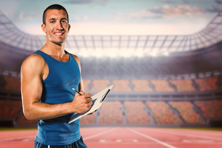 sports coach: Portrait of confident sports coach writing on clipboard against race track