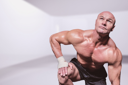 against abstract: Bodybuilder exercising against black background against abstract room