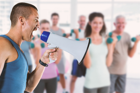 outraged: Composite image of angry male trainer yelling through megaphone