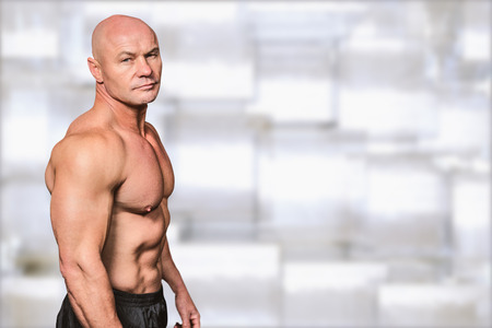 against abstract: Portrait of shirtless bald man against abstract background