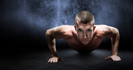 push: Confident shirtless athlete doing push ups against dark background