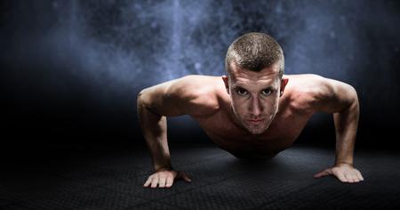 push ups: Confident shirtless athlete doing push ups against dark background