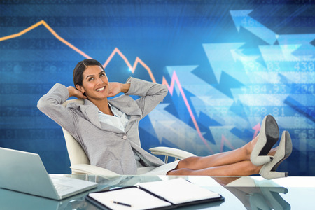 swivel chair: Businesswoman relaxing in a swivel chair against stocks and shares