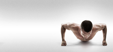 strength training: Fit shirtless athlete doing push ups against grey background Stock Photo