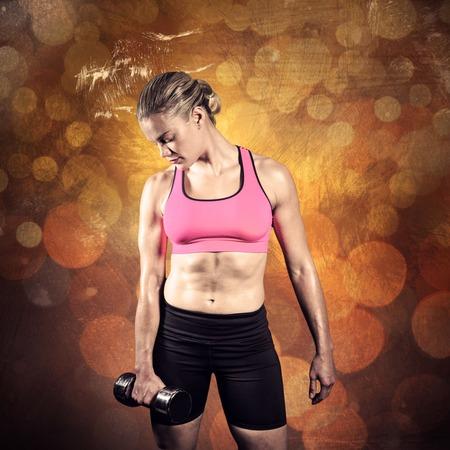 mottled: Muscular woman lifting heavy dumbbell against dark background
