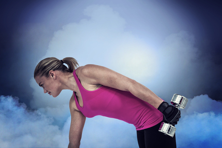 weightlifting gloves: Muscular woman exercising with dumbbells  against cloudy sky