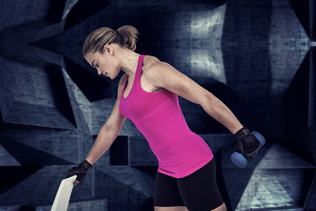 weightlifting gloves: Muscular woman exercising with dumbbells  against dark room